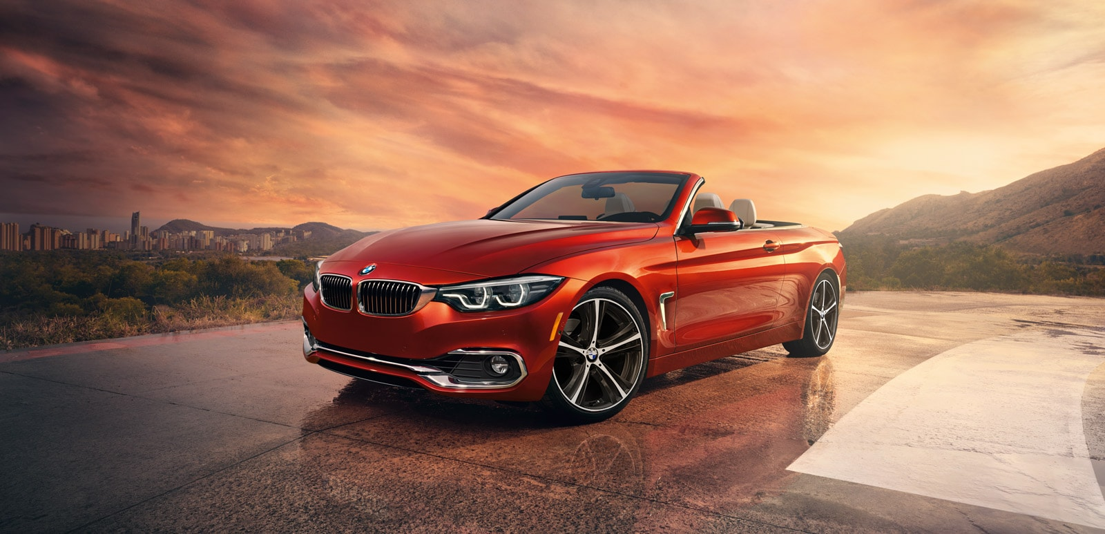 A 2019 BMW 4 Series Convertible with the top down parked overlooking a cityscape