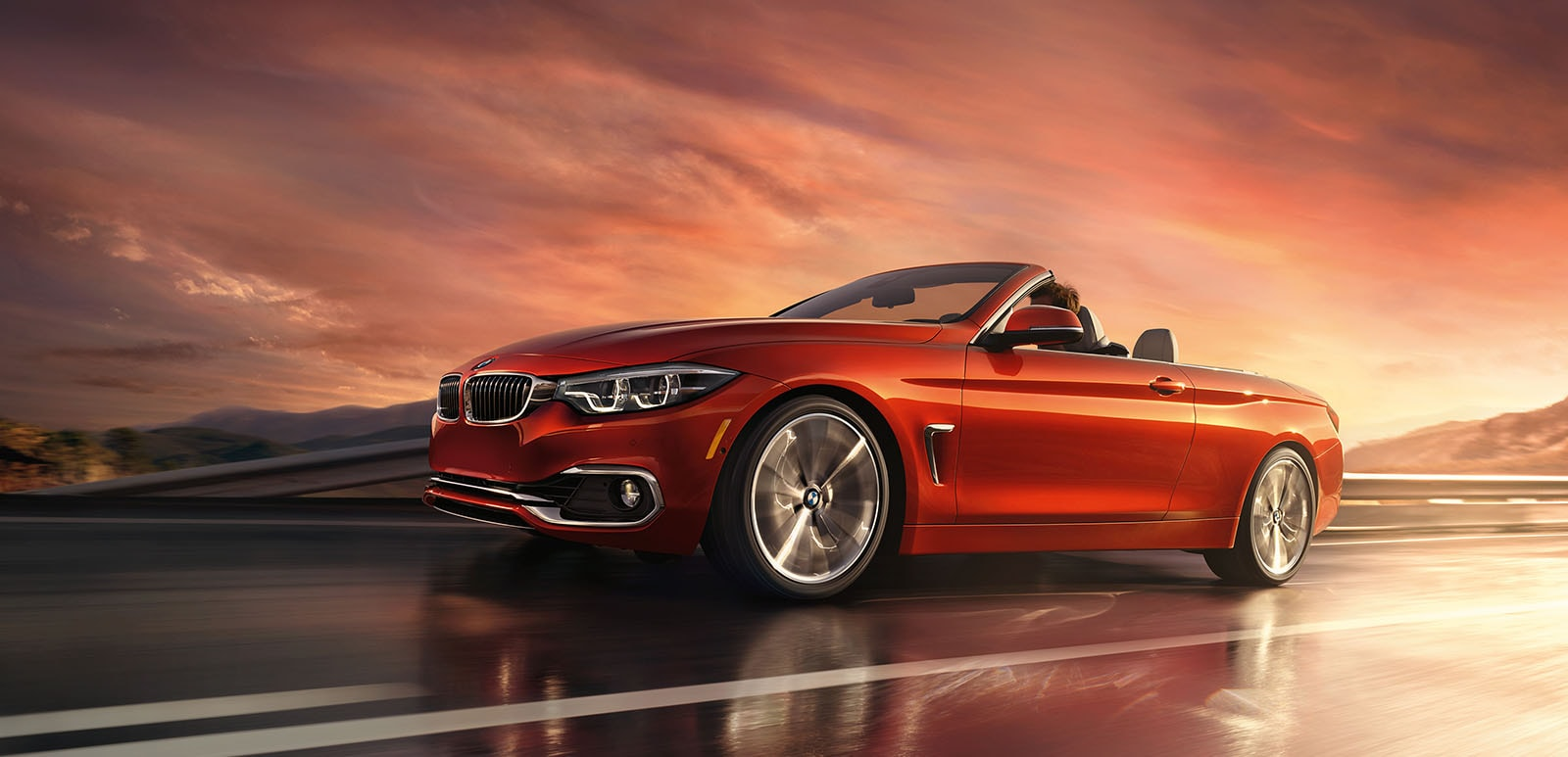 A 2019 BMW 4 Series Convertible driving at sunset
