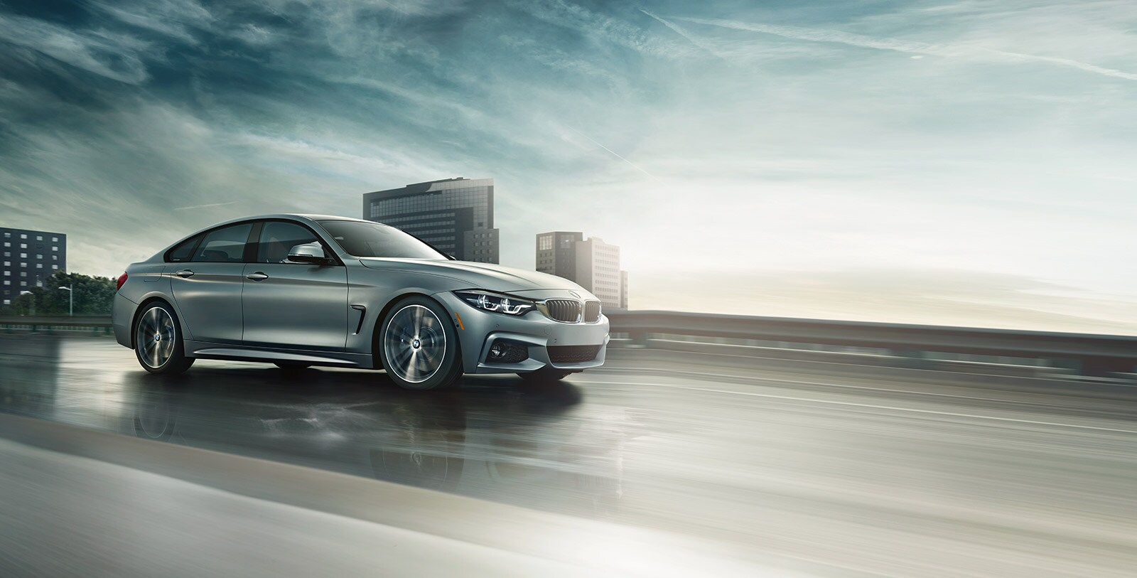 A 2019 BMW 4 Series Gran Coupe driving in front of a city skyline