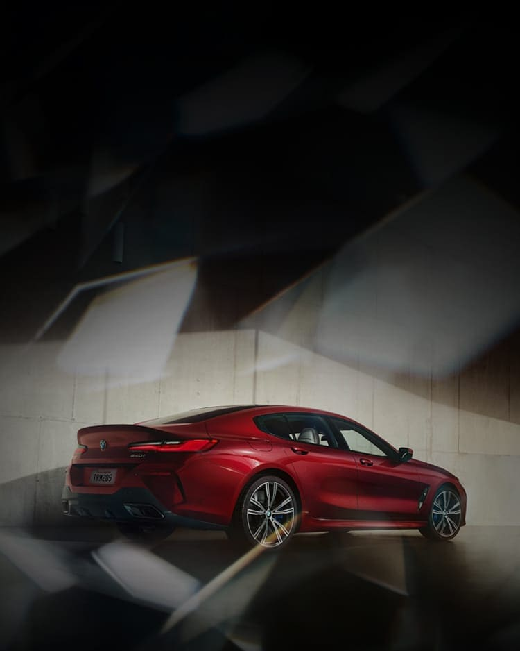 A rear quarter view of a BMW 840i Gran Coupe in Aventurin Red Metallic