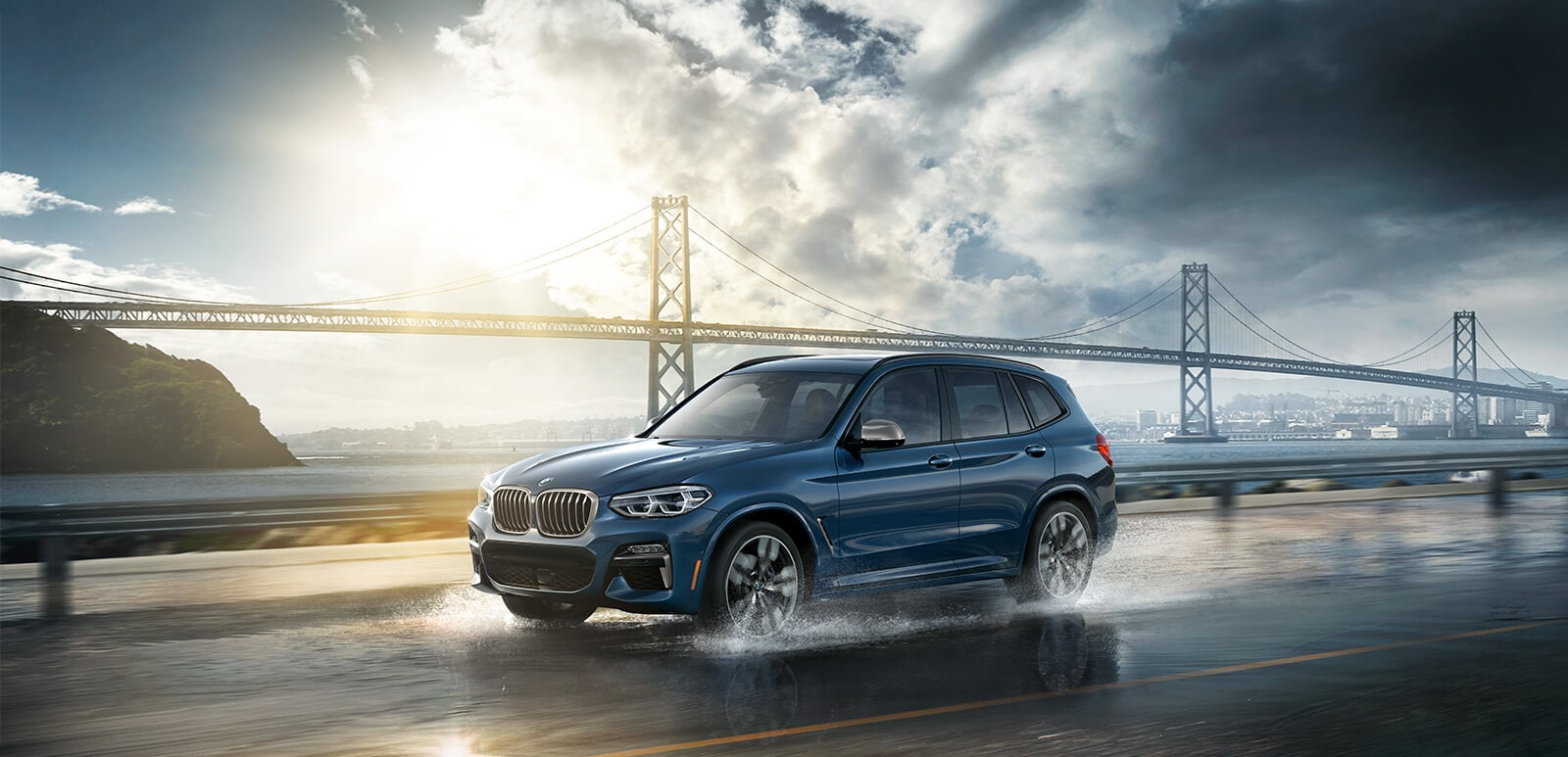 A 2018 BMW X3 M40i drives along a damp road in front of a long suspension bridge
