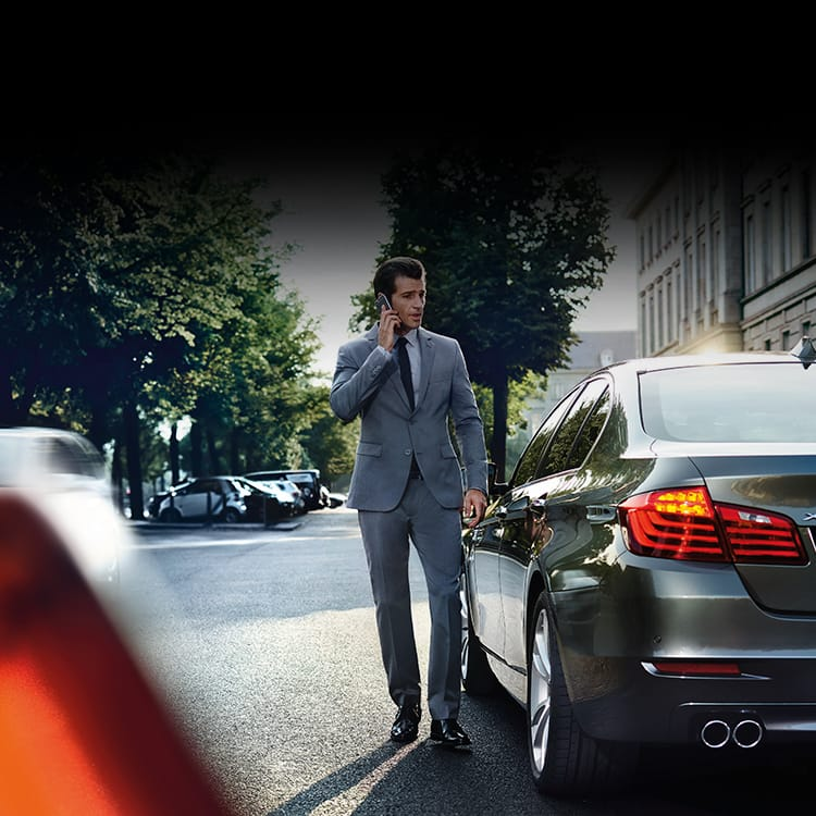 BMW driver in grey suit reporting an incident on the phone standing next to his BMW